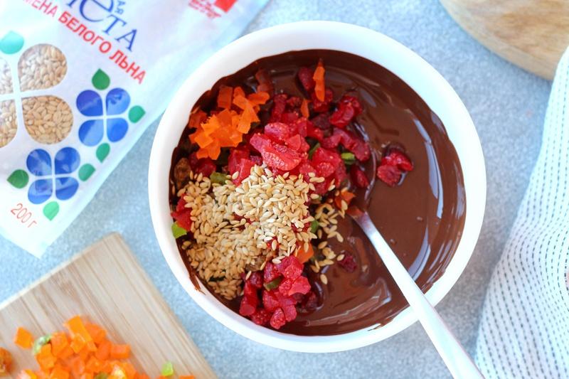 Семена льна и сухофрукты в миске с растопленным шоколадом